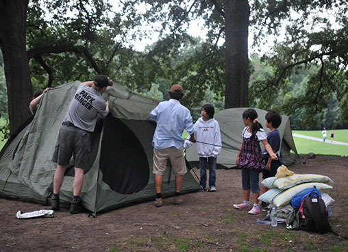 A park ranger helps a family set up a tent in the park