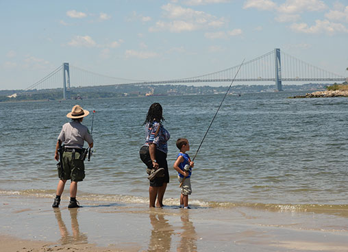 A park ranger shows a family how to use fishing rod to go fishing at the waterfront
