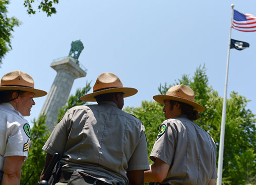 Park rangers walk up to a monument in a park