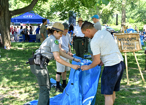 A park ranger shows a park guests how to set up a tent