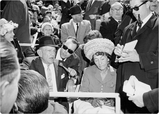 Image of Mets manager Casey Stengel and his wife Edna with reporters at Shea Stadium Opening Day, April 16, 1964. Neg. 31964.2