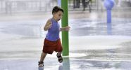 A child running through a spray shower.