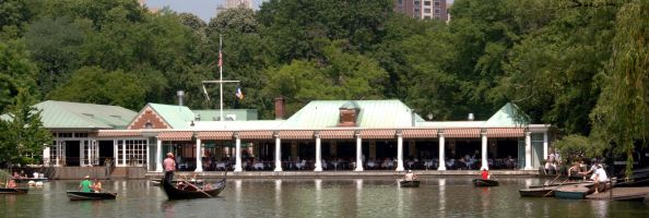 Gondoliers help paddle along the lake in front of Central Park's boathouse.