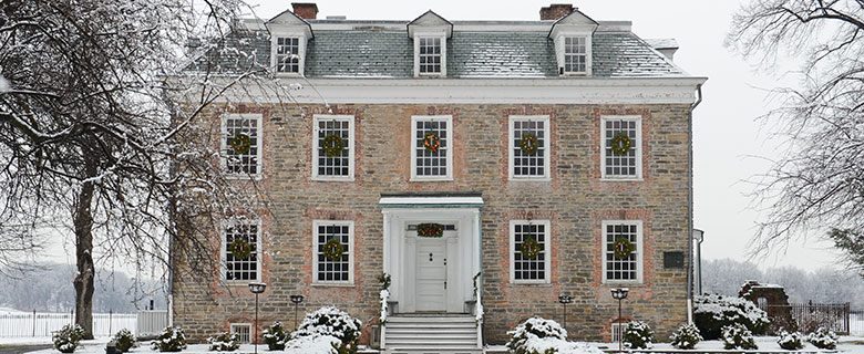 a mansion with wreaths on the windows in a park on a snowy day