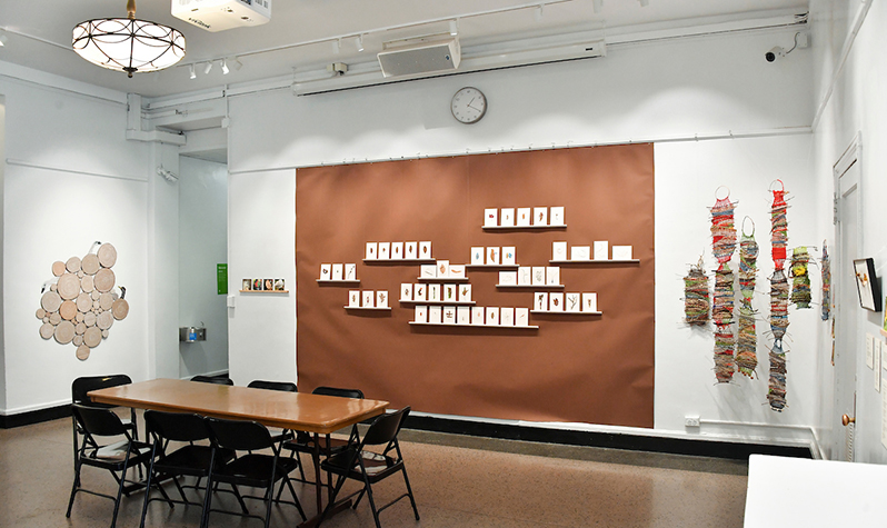 View from the gallery floor of Alice's artwork on display on three walls. To the left, an arrangement of cardboard looks like tree barks, at the center wall leaves arranged on paper is displayed on a brown wall, and to the right are weavings arranged as structures.