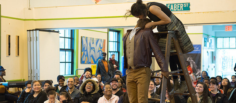 The crowd in the rec center looks on in awe as an actress playing Juliet leans in from the steps on a ladder to give Romeo a kiss upside down.