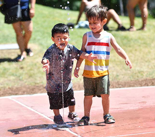 Two children enjoy a spray of water from a spray shower