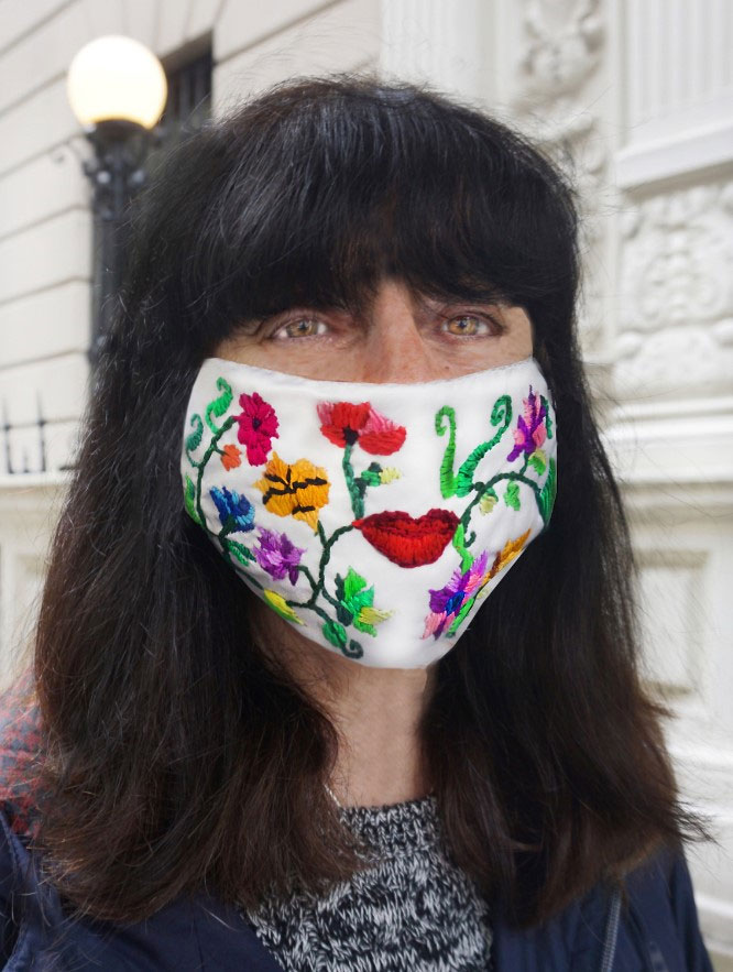 The artist wears a mask that features flowers, plants, and lips embroidered on it