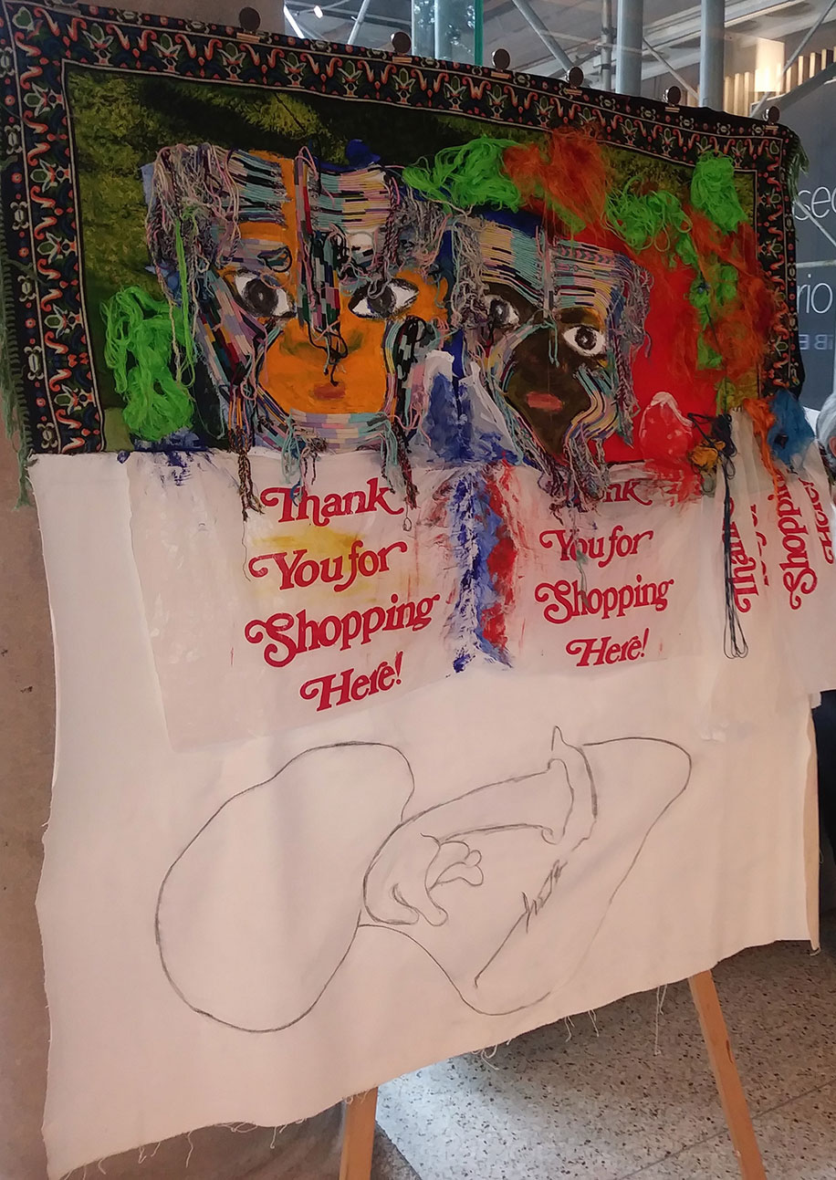 A hanging canvas of two faces, each above shopping bags that read Thank Your for Shopping Here; below the bags is an outline of someone propping their chin while lying down and looking up