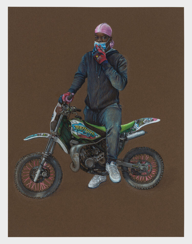 A Black biker wearing a pink dur rag holds a blue mask to his face while standing over his bike