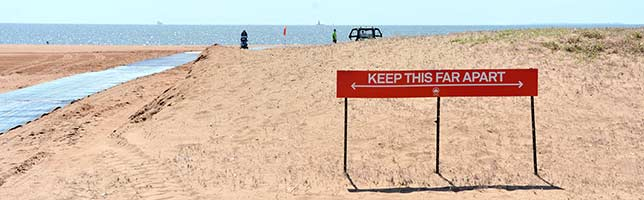 A red social distancing sign at the beach reads: Keep This Far Apart.