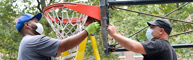 The operations crew re-install hoops at the basketball court after playing basketball in parks resumed