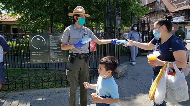 An urban park ranger distributes masks to a mother walking with her child in front of a park.