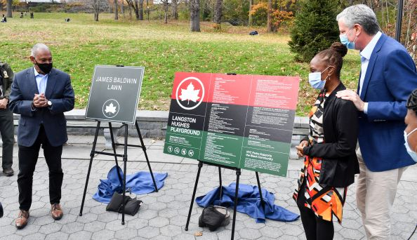 "Mayor Bill de Blasio, First Lady Chirlane McCray, and Parks Commissioner Mitchell J. Silver look at signs that read ""James Baldwin Lawn"" and ""Langston Hughes Playground."""