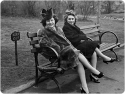 Two women pose on a park bench.