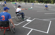 Athletes in wheelchairs play softball