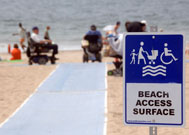 Sign on beach next to beach mat reads Beach Access Surface