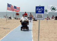 Man in wheelchair on beach mat next to sign reading Beach Access Path