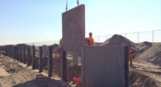 sections of sand retaining wall being lowered in place