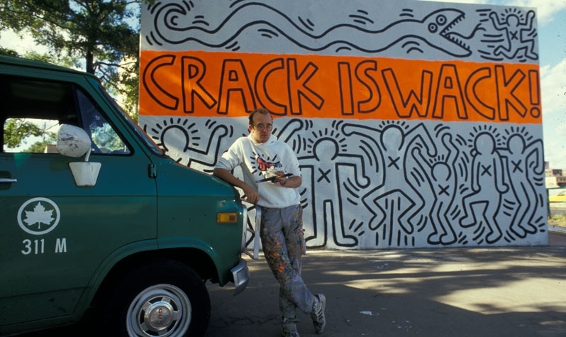 Keith Haring leans on a green parks van in front of his famous Crack is Wack mural, and orange and white artwork featuring chalk-like outlines of people with Xs on their chests.