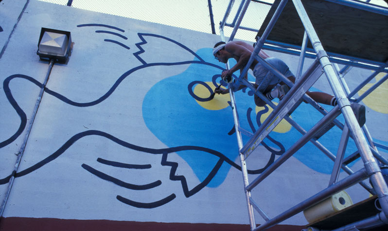 Keith Haring uses a scaffold to paint an outline of a fish with blotches of yellow and blue on the wall of the outdoor pool in what is now Tony Dapolito Park.
