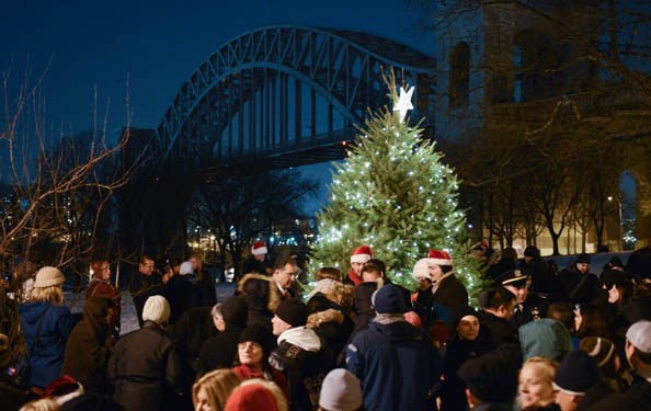 carolers gather at a decorated Christmas tree against the backdrop of the Hell Gate bridge at night