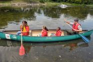 An Urban Park Ranger leads a canoe of children
