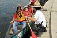 An Urban Park Ranger assists children eager to canoe the restored lake