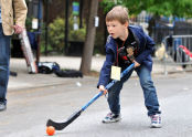 A boy playing street hockey.