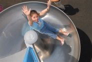 A girl tries out the playground's slide