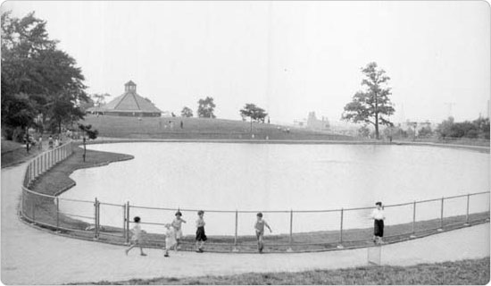 One of the earliest shots of a carousel in a New York City park.  The carousel peeks up from above the pond at Sunset Park, July 25, 1934.  Courtesy of Parks Photo Archive, Neg. 3538.