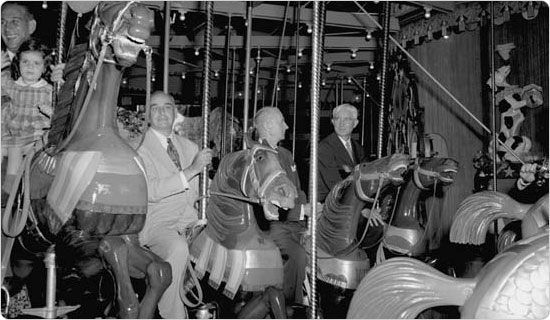 Parks Commissioner Robert Moses and Mayor Vincent Richard Impellitteri take a spin on the then-newly dedicated carousel in Central Park, July 2, 1951.  Courtesy of Parks Photo Archive, Neg. 53510.9.